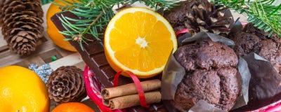 Feche acima dos maffins, das laranjas e do chocolate no fundo da árvore de Natal Imagem de Stock Royalty Free