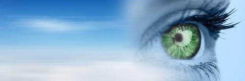 Feche acima dos olhos azuis com íris verde e transição obscura do céu Fotografia de Stock Royalty Free