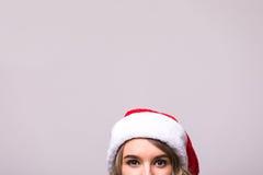 Feche acima dos olhos das meninas no chapéu de Santa do Natal Imagem de Stock Royalty Free
