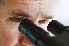 Feche acima dos olhos do homem que olham através do microscópio Imagens de Stock