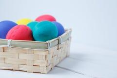 Feche acima dos ovos da páscoa coloridos em de madeira Fotos de Stock