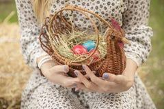 Feche acima dos ovos da páscoa coloridos em uma cesta Fotografia de Stock