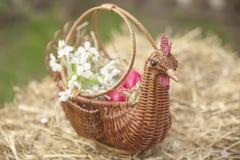 Feche acima dos ovos da páscoa coloridos em uma cesta Imagens de Stock