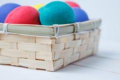 Feche acima dos ovos da páscoa coloridos na cesta Foto de Stock