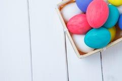 Feche acima dos ovos da páscoa coloridos na cesta Fotos de Stock