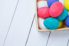 Feche acima dos ovos da páscoa coloridos na cesta Imagem de Stock
