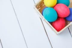 Feche acima dos ovos da páscoa coloridos na superfície de madeira na cesta Fotos de Stock