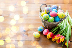 Feche acima dos ovos da páscoa na cesta e nas flores Imagem de Stock