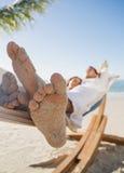 Feche acima dos pés arenosos dos pares que dormem em uma rede Fotografia de Stock