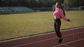 Feche acima dos pés da aptidão-mulher que saltam, usando a corda de salto no estádio vídeos de arquivo