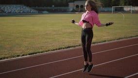 Feche acima dos pés da aptidão-mulher que saltam, usando a corda de salto no estádio filme