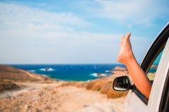 Feche acima dos pés da menina que mostram do mar do fundo da janela de carro Imagem de Stock Royalty Free