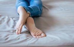 Feche acima dos pés da mulher com calças de ganga, pés e estiramento preguiçosamente Fotografia de Stock