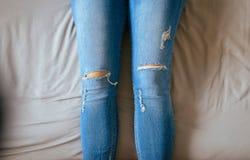 Feche acima dos pés da mulher com calças de ganga, pés e estiramento preguiçosamente na cama Imagem de Stock Royalty Free