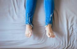 Feche acima dos pés da mulher com calças de ganga, pés e estiramento preguiçosamente na cama Foto de Stock Royalty Free
