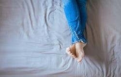 Feche acima dos pés da mulher com calças de ganga, pés e estiramento preguiçosamente na cama Fotografia de Stock Royalty Free