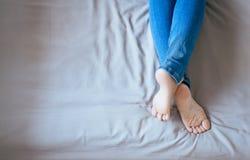 Feche acima dos pés da mulher com calças de ganga, pés e estiramento preguiçosamente na cama Fotos de Stock