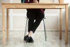 Feche acima dos pés da senhora do negócio na mesa que antecipa a reunião imagem de stock