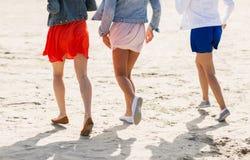 Feche acima dos pés das mulheres que correm na praia Foto de Stock Royalty Free