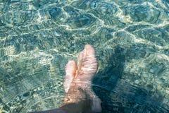 Feche acima dos pés descalços do homem da imagem na água do mar imagens de stock royalty free