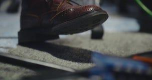 Feche acima dos pés do guitarrista que ajustam o ritmo filme