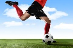 Feche acima dos pés do jogador de futebol em peúgas vermelhas e nas sapatas pretas que correm e que retrocedem a bola na ação liv Fotografia de Stock Royalty Free