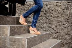 Feche acima dos pés do ` s da menina em ir abaixo das escadas Fotografia de Stock