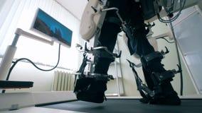 Feche acima dos pés do ` s do homem nas ligações de uma máquina do treinamento durante exercícios de passeio Robótico médico elet filme