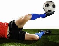 Feche acima dos pés e da sapata do futebol do jogador de futebol na ação que faz o equipamento e que retrocede a bola Fotografia de Stock Royalty Free