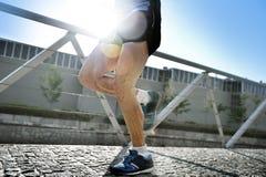 Feche acima dos pés e das sapatas da corrida praticando do homem atlético novo no luminoso de aumentação natural do fundo urbano imagens de stock