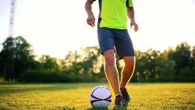 Feche acima dos pés e dos pés do jogador de futebol na ação que veste as sapatas pretas que correm e que pingam com a bola que jo video estoque