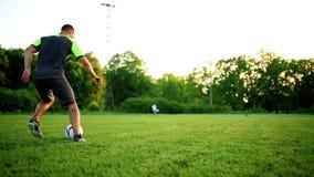 Feche acima dos pés e dos pés do jogador de futebol na ação que veste as sapatas pretas que correm e que pingam com a bola que jo filme
