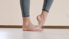 Feche acima dos pés fêmeas da aptidão que fazem esticando o exercício Exercício da jovem mulher interno vídeos de arquivo