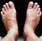 Feche acima dos pés masculinos nas escalas de vidro do assoalho digital preto foto de stock royalty free