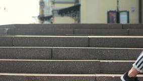 Feche acima dos pés dos pares novos que andam abaixo das escadas filme