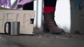 Feche acima dos pés que movem-se nas sapatas marrons de couro na rua devido ao frio ao lado de um sinal na caixa de ajuda video estoque
