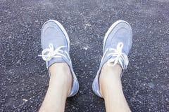 Feche acima dos pés que vestem as sapatilhas azuis Imagens de Stock