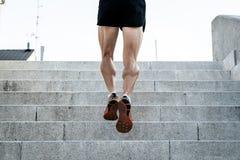 Feche acima dos pés running do homem no por do sol em uma estrada secundária foto de stock