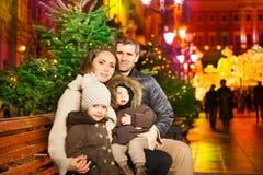 Feche acima dos pais e das crianças que sentam-se no parque da cidade Fotografia de Stock Royalty Free