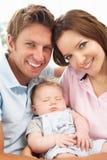 Feche acima dos pais que afagam o bebé recém-nascido em H Imagens de Stock