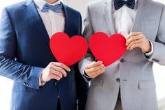 Feche acima dos pares alegres masculinos que guardam corações vermelhos imagens de stock
