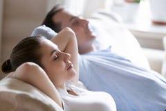 Feche acima dos pares calmos que relaxam no sofá acolhedor imagens de stock