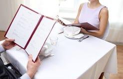 Feche acima dos pares com menu no restaurante fotografia de stock royalty free