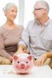 Feche acima dos pares com moedas e mealheiro Fotografia de Stock Royalty Free