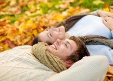 Feche acima dos pares de sorriso que encontram-se no parque do outono Fotos de Stock Royalty Free