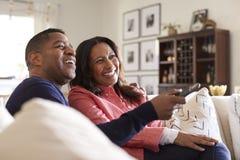 Feche acima dos pares envelhecidos médios que sentam-se no sofá em sua sala de visitas usando a tevê remota e olhando, rindo, fim imagens de stock