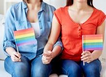 Feche acima dos pares lésbicas com bandeiras do arco-íris fotografia de stock royalty free