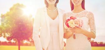 Feche acima dos pares lésbicas felizes com flores foto de stock