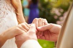 Feche acima dos pares no casamento que guarda as mãos Fotos de Stock Royalty Free