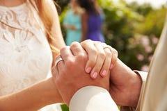 Feche acima dos pares no casamento que guarda as mãos Imagem de Stock